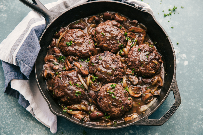 Hamburger Steak in a skillet with mushroom and onion gravy-perfect for the whole family.