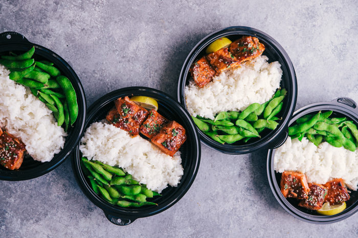 maple glazed salmon with white ride and edamame in black bowls for meal prep, by The Food Cafe