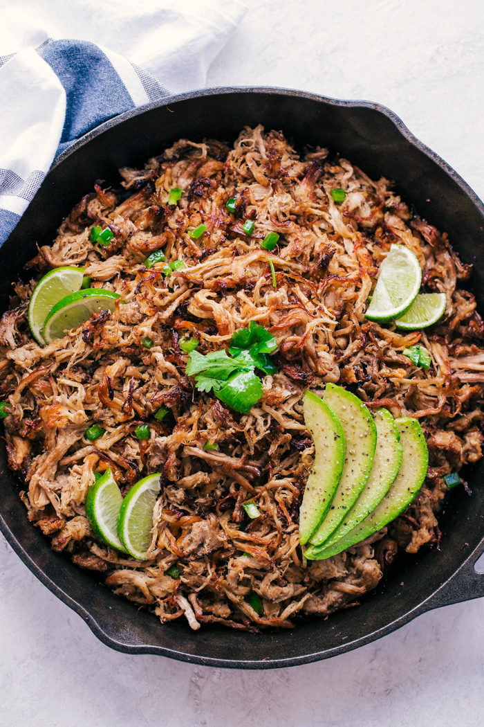 pork carnitas meat in a black skillet served with sliced limes and avocados by The Food Cafe