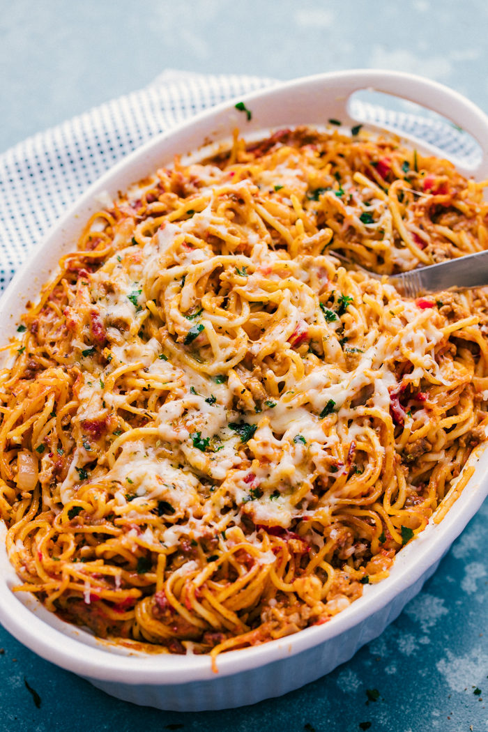 baked spaghetti being served from a white baking dish with a silver serving spoon.