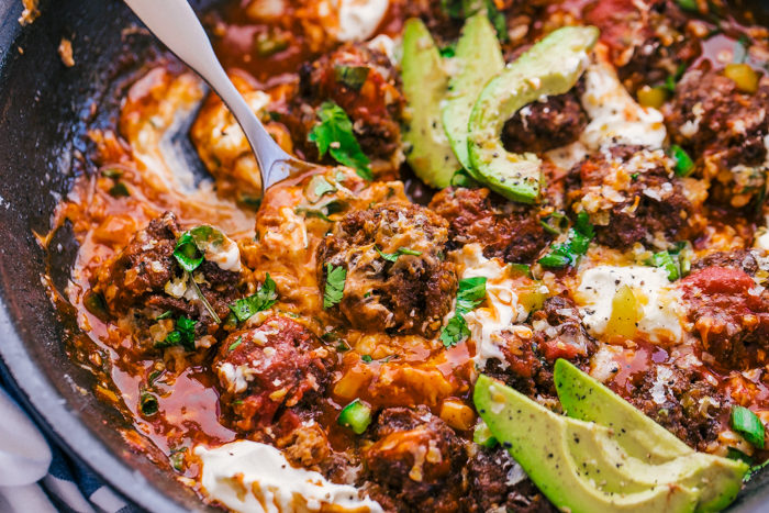 Enchilada meatballs cooked in a black skillet with cheese, sour cream, sauce, and sliced avocado for the perfect easy dinner, by The Food Cafe.