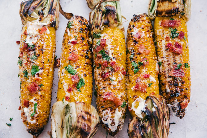 grilled corn on the cob with husks on on a white plate topped with chopped bacon, parmesan cheese, butter and cilantro by The Food Cafe