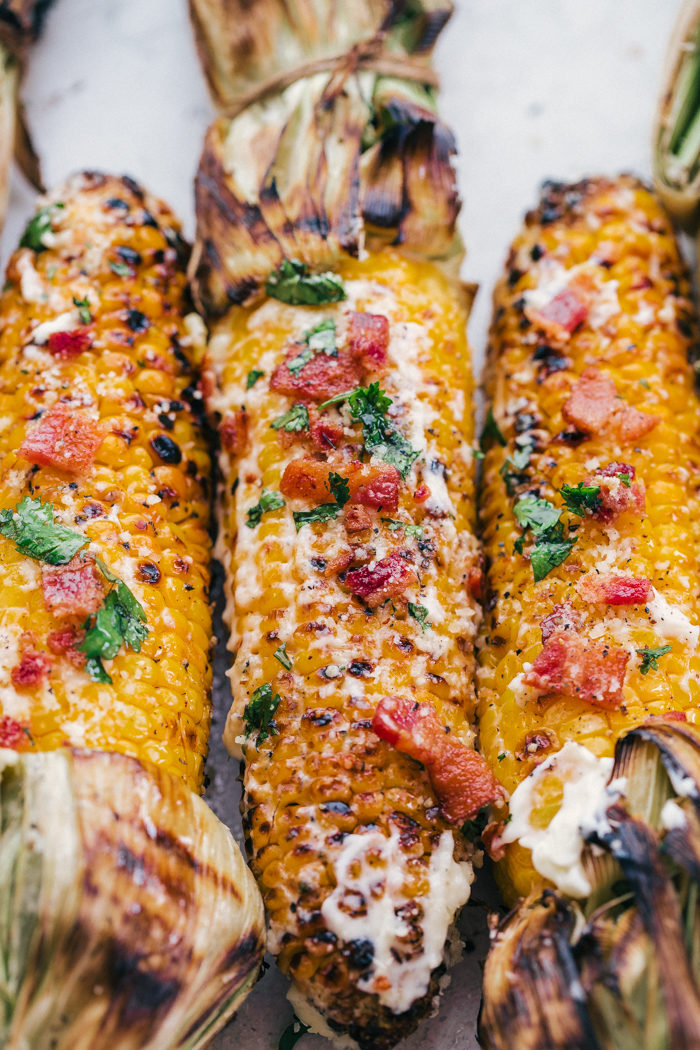 corn on the cob on the grill topped with butter, chopped bacon, and diced cilantro by The Food Cafe.