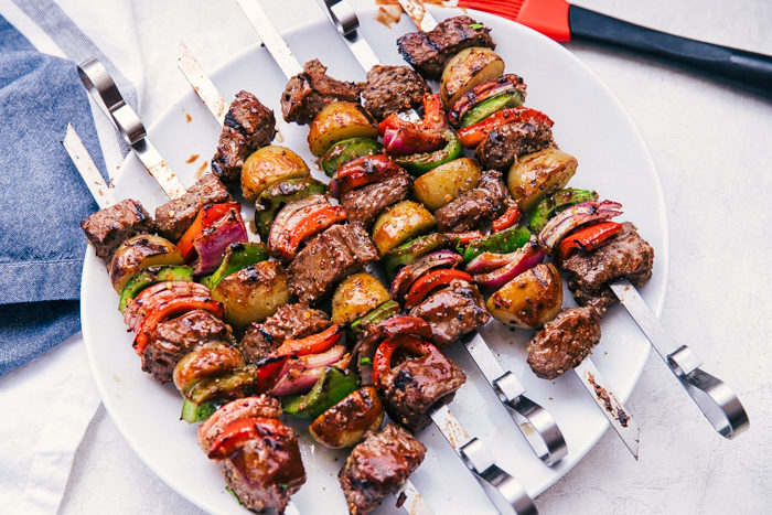 shish kabobs made with beef, peppers and onions on metal skewers served on a white plate by The Food Cafe.