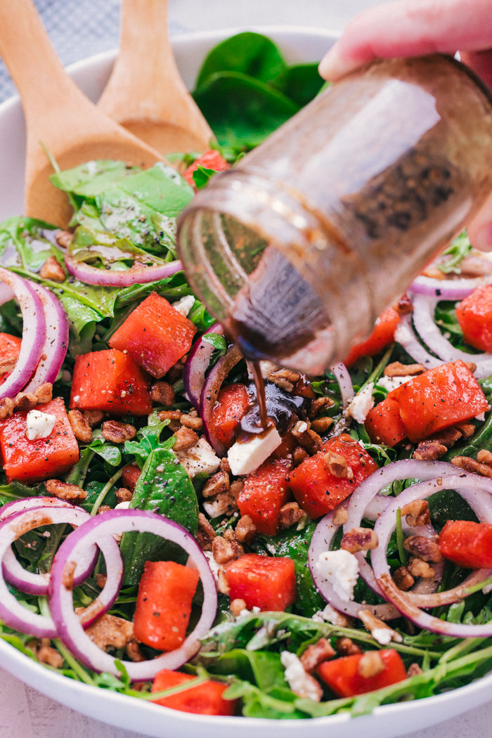 Watermelon salad filled with spinach, red onions, feta cheese and roasted walnuts with salad dressing being drizzled on top by The Food Cafe.