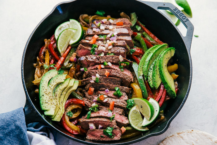steak fajitas made in a black skillet served with cooked sliced pepper, sliced avocados, and lime wedges by The Food Cafe.