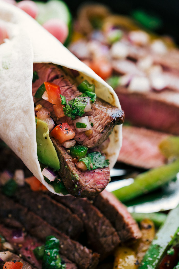 steak fajitas wrapped in a flour tortilla with peppers, pico de gallo, and sliced avocados by The Food Cafe.