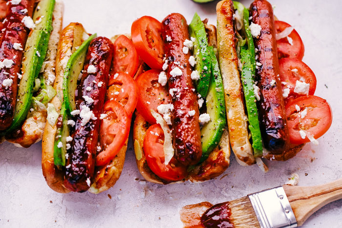 California Hot Dogs with sliced tomatoes, avocado and diced onions on a white background by The Food Cafe.