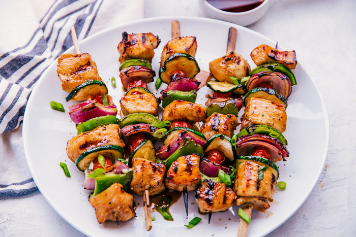 chicken kabobs made with teriyaki sauce, red onion and zucchini on a wooden skewer served on a white place by The Food Cafe.