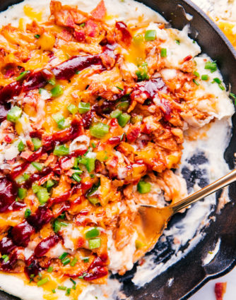 bbq chicken in a skillet with mashed potatoes, melted cheese and bacon