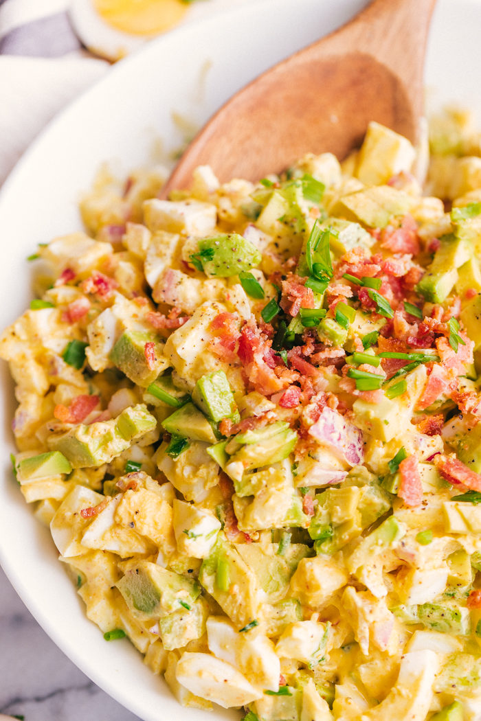 Curried egg salad in a white bowl with bacon and chives on top