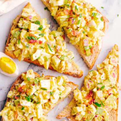 Egg salad on top of whole wheat bread with bacon and chives