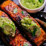 two salmon filets in skillet with avocado sauce on top