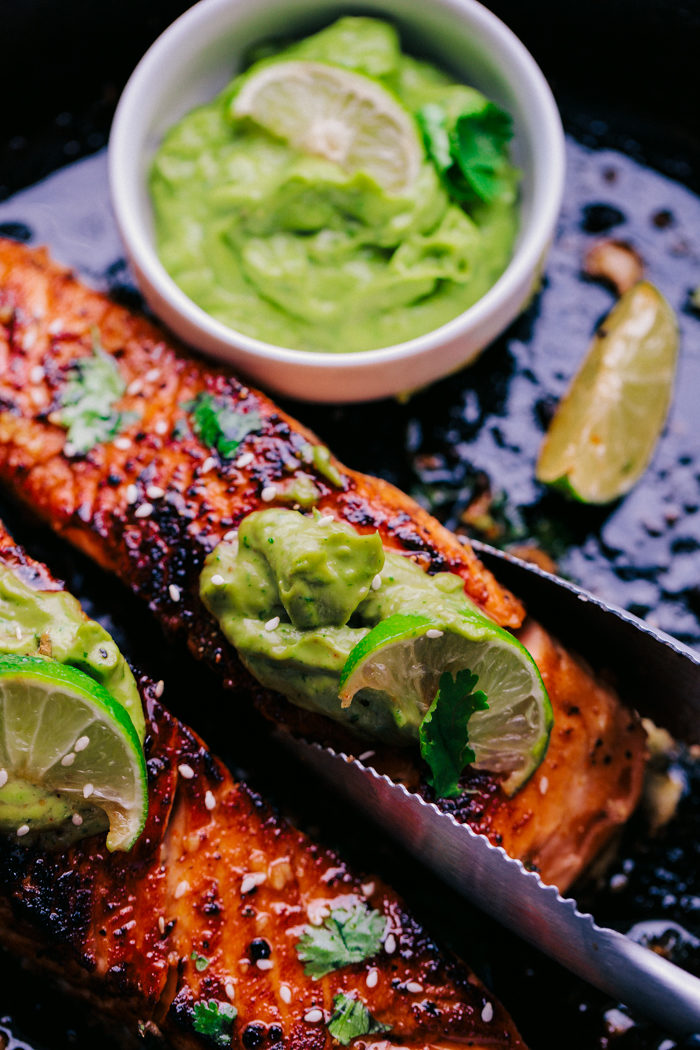 Salmon in skillet with avocado sauce on top and thongs removing a piece