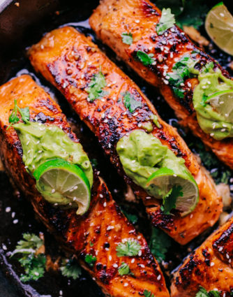 Salmon cooked in skillet with avocado sauce, cilantro and sliced limes on top