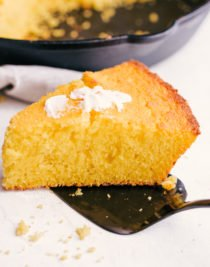 the best skillet cornbread on a spatula with butter on top