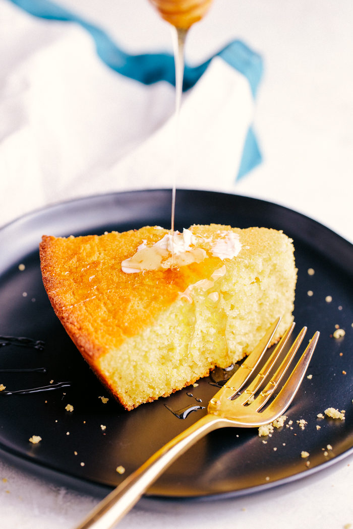 the best skillet cornbread on a plate drizzled with honey