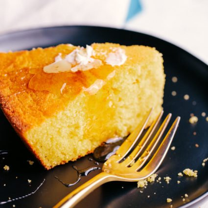 The best skillet cornbread sliced on a plate with butter and honey