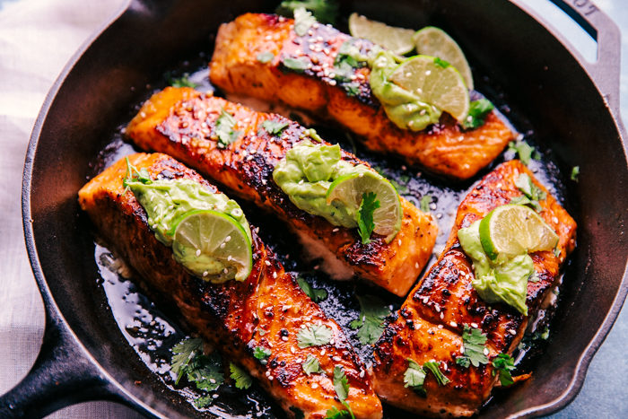 Salmon with creamy avocado sauce in skillet