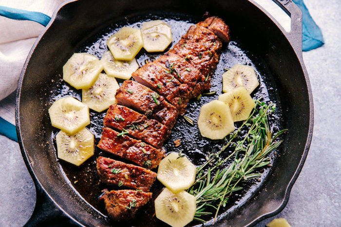 Brown Butter Pork Tenderloin in a skillet with a sprig of rosemary and sliced kiwis