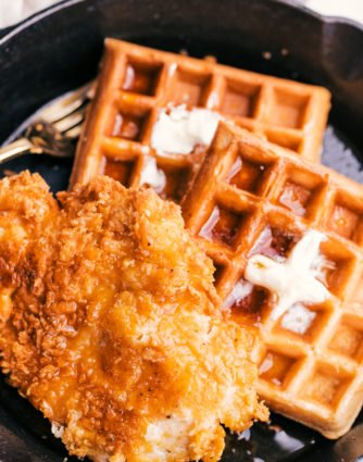 fried chicken and waffles with butter and syrup on a skillet