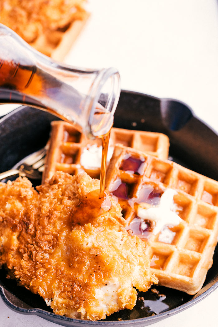 fried chicken and waffles in a skillet with syrup poured on top.