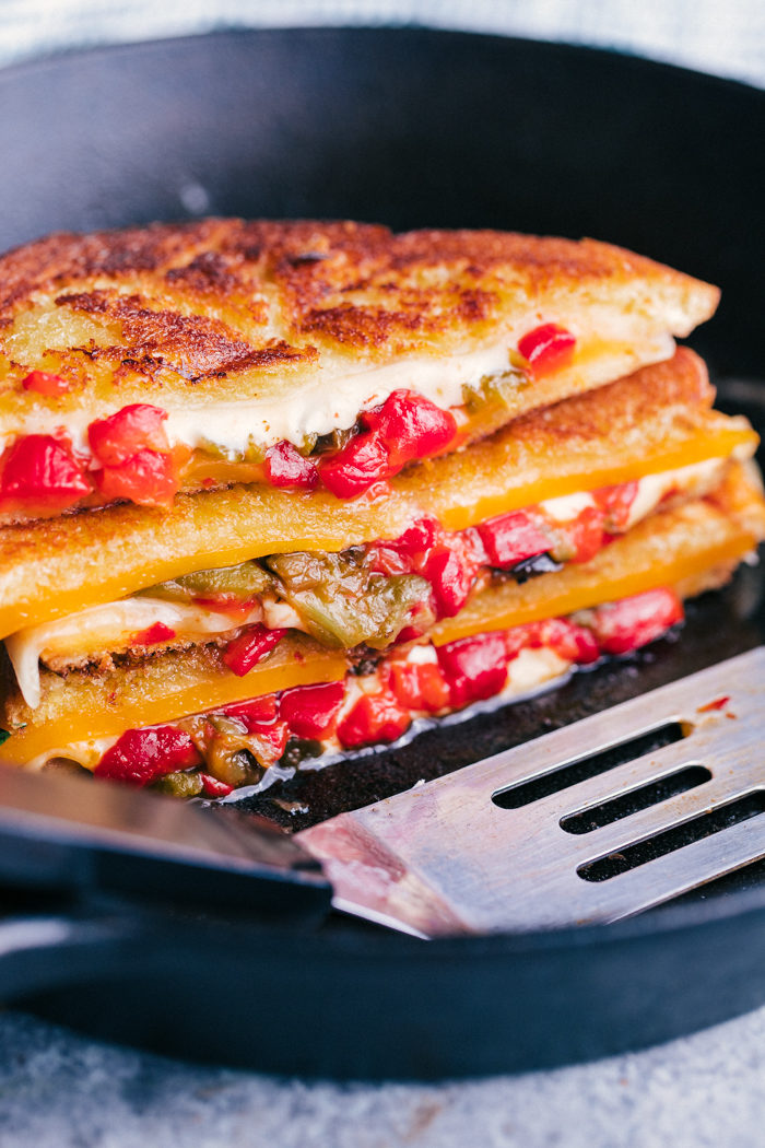 Grilled cheese sandwich stacked in a skillet with cheese and peppers oozing out.