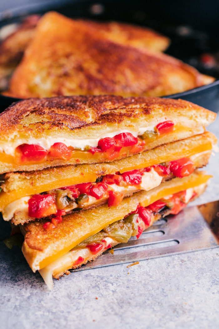 Grilled Cheese Sandwich stacked on top of each other sliced in half with melted cheese and peppers