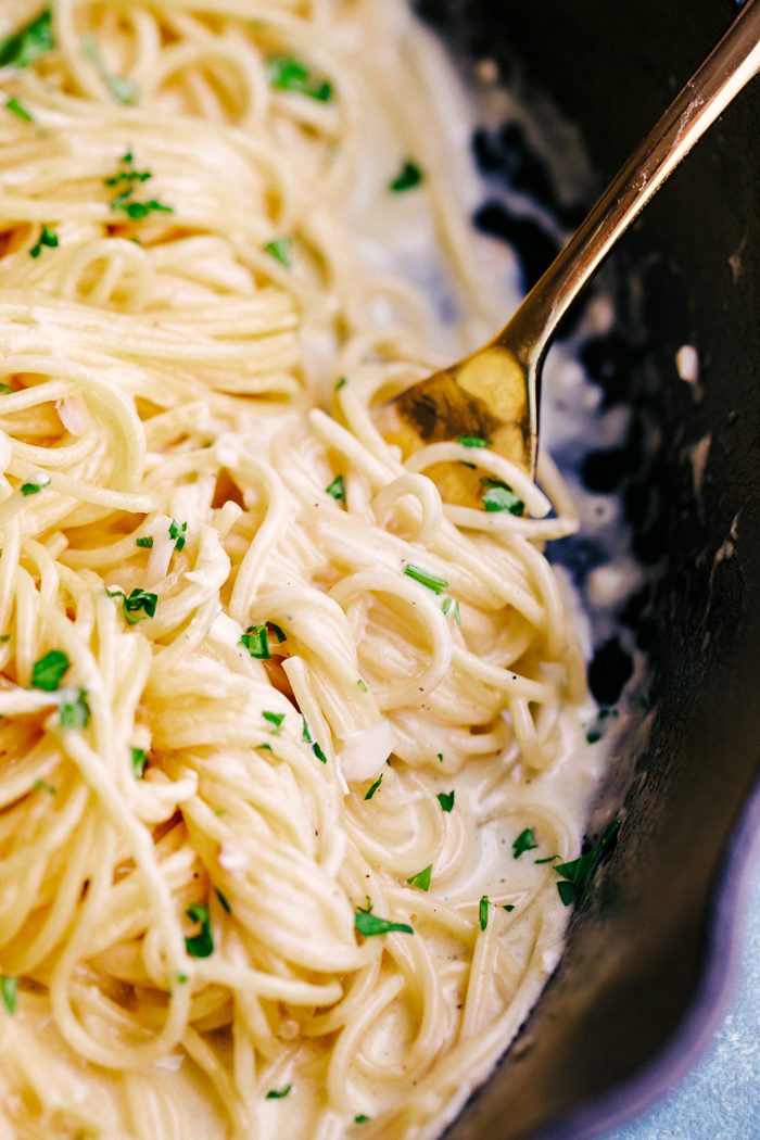 Parmesan Garlic butter noodles wrapped around a fork with creamy sauce.