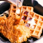 chicken and waffles in skillet with syrup being poured on top