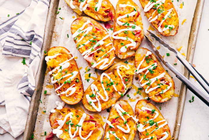 cheese and bacon potato skins on a sheet pan topped with chives and sour cream by The Food Cafe