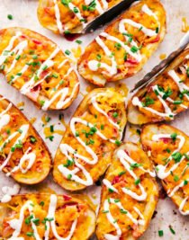 cheddar and bacon potato skins on a sheet pan with ranch dressing and chives on top