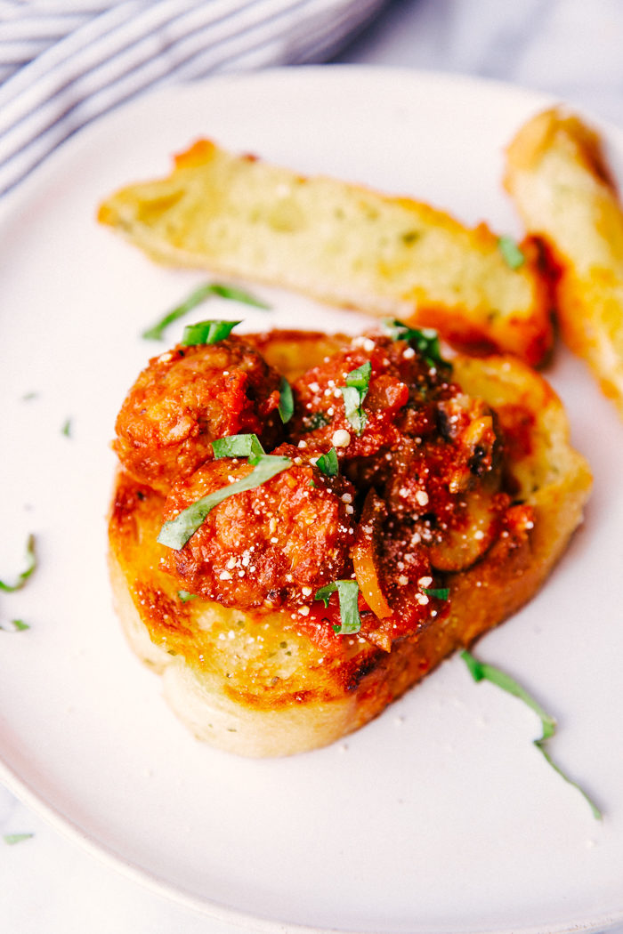 cheesy skillet meatballs being served on garlic bread on a white plate.