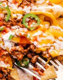 chili cheese nachos served on a sheet pan