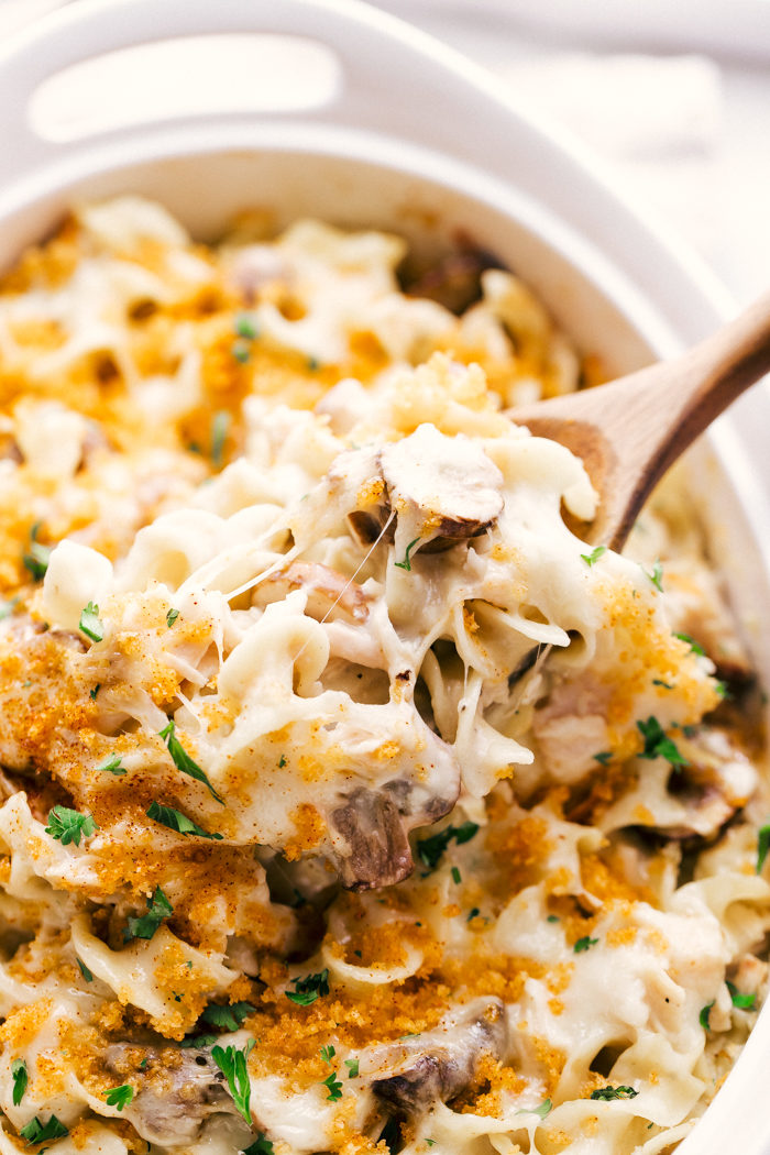 Easy Creamy Chicken Mushroom Casserole being served out of a white dish with a wooden spoon.