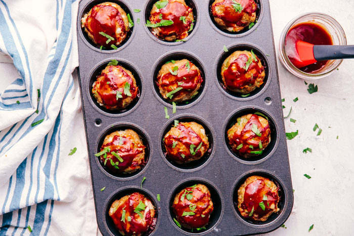 muffin tin meatloaf in a muffin tin being topped with BBQ sauce.