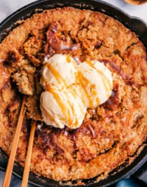 pumpkin cobbler in a skillet with ice cream and 2 spoons
