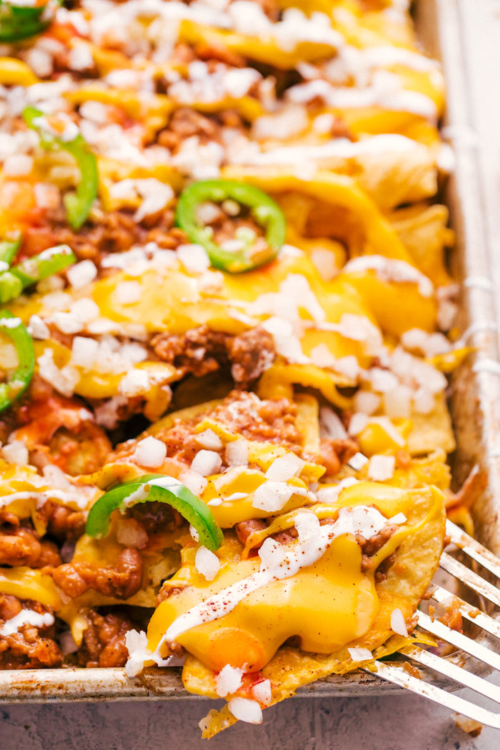 Sheet pan chili cheese nachos served from a rimmed sheet pan with melted cheese, ground beef, diced onions, and jalapeños by The Food Cafe
