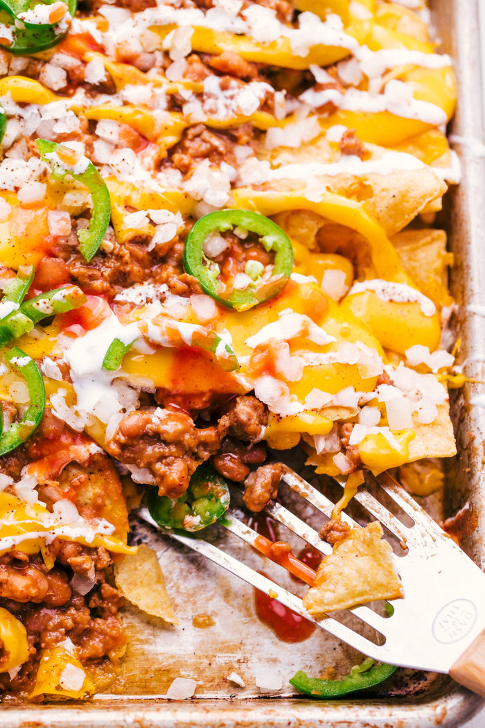 sheet pan chili cheese nachos being served with a spatula, by The Food Cafe