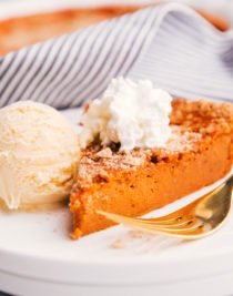 a slice of easy healthy crustless pumpkin pie on a plate with ice cream and whipped topping.