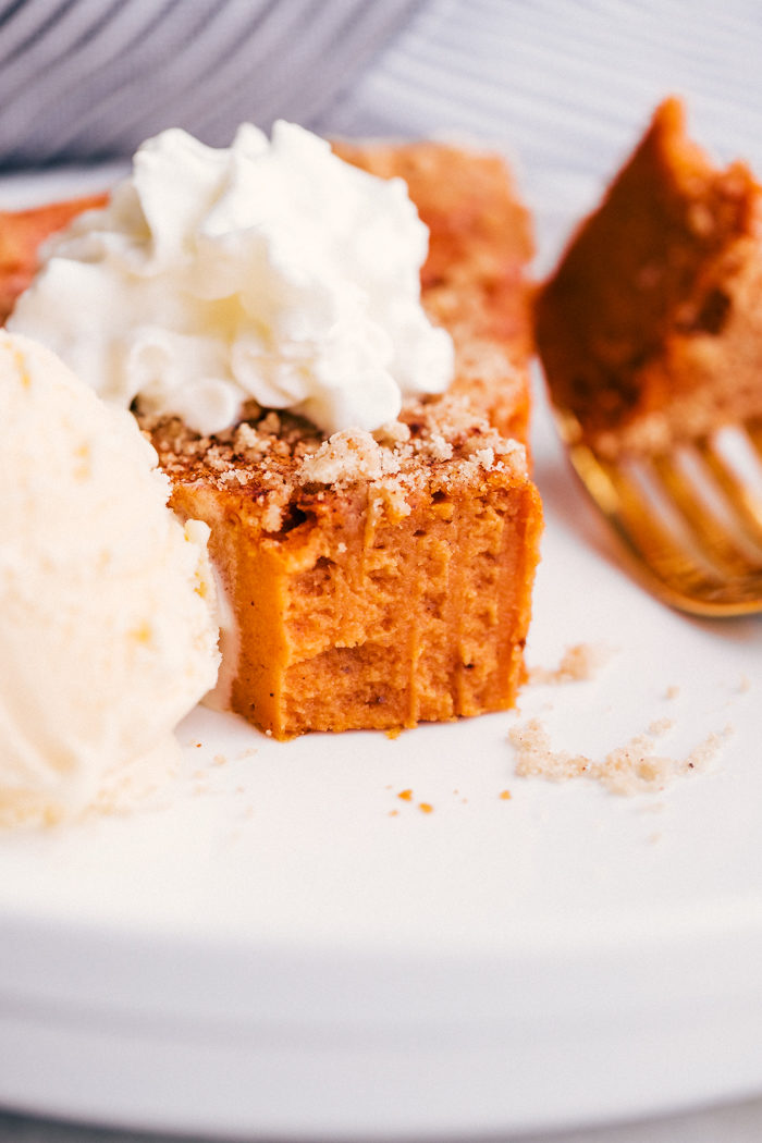 easy healthy crustless pumpkin pie on a white plate topped with ice cream and whipped cream.