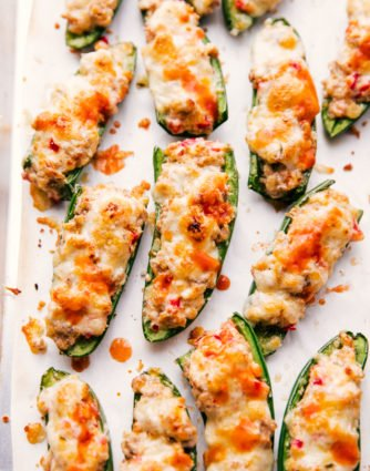 Stuffed jalapeno poppers served on a sheet pan with melted cheese and hot sauce on top.