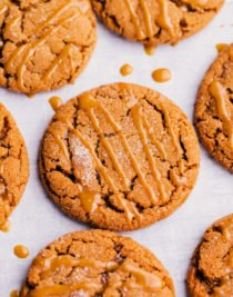 Chewy ginger cookies on a cooling rack with molasses glaze