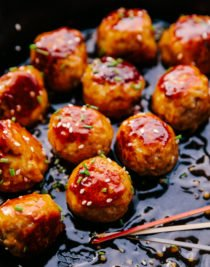 honey garlic meatballs in a cast iron skillet with cocktail toothpicks to eat them with.