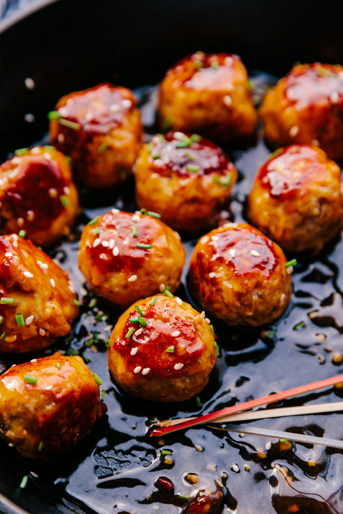 honey garlic meatballs in a cast iron skillet glazed with honey garlic sauce, diced chives, and sesame seeds.