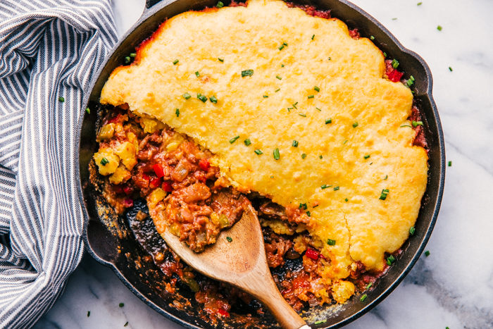 sloppy joe cornbread being served with a wooden spoon out of a skillet-ready in 20 minutes.