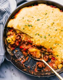 Sloppy joe cornbread casserole in cast iron skillet eaten with gold spoon.