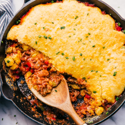 sloppy joe cornbread casserole in a skillet being served with wooden spoon.