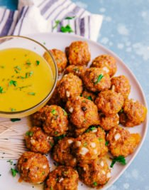 spicy sausage cheese balls loaded on a white plate with cheese dip.
