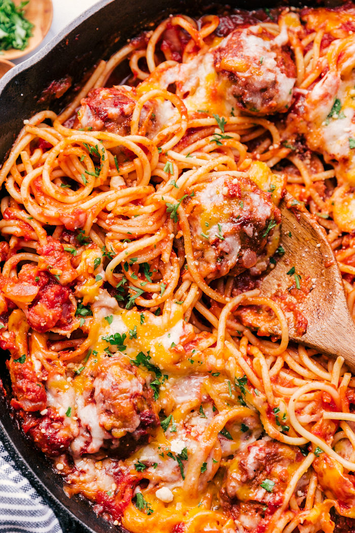 baked spaghetti casserole with meatballs being served out of a skillet with wooden spoon.